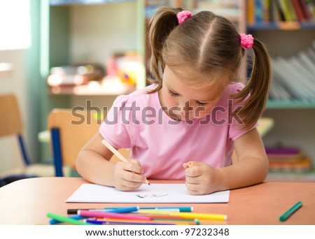 Cute little girl is drawing with felt-tip pen in preschool - stock photo