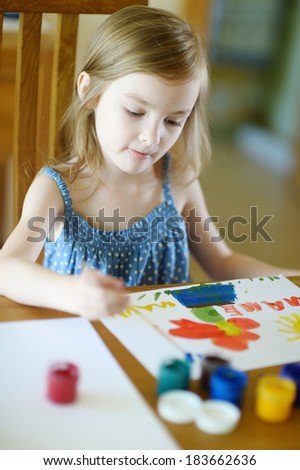 Cute little girl is drawing with paints in preschool