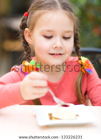 Cute little girl is eating cake in parlor
