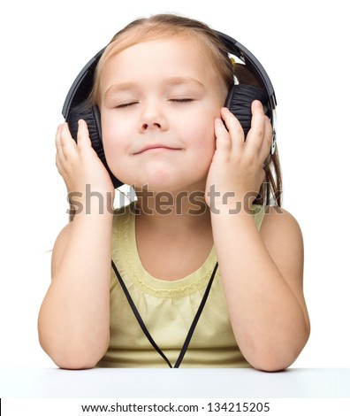 Cute little girl is enjoying music using headphones while closed her eyes, isolated over white