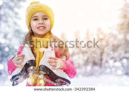 cute little girl is going skate outdoors