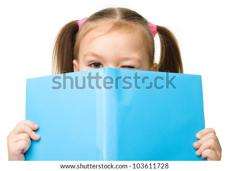 Cute little girl is hiding behind a book, isolated over white