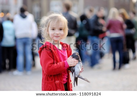 Cute little girl is holding a pigeon