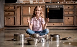 Cute little girl is holding wooden spoons, looking at camera and smiling while playing drums with dishes in kitchen