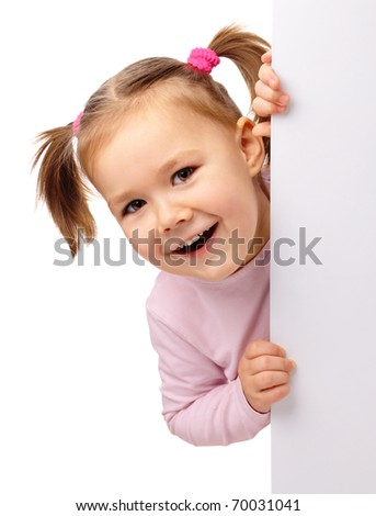 Cute little girl is laughing while bending over blank board, isolated on white