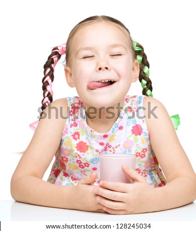 Cute little girl is licking her lips while drinking milk, isolated over white
