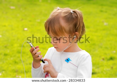 Cute little girl is listening to music outdoor #28334833