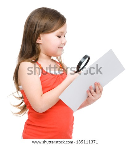 Cute little girl is looking at big paper sheet through magnifier, isolated over white