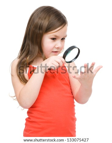 Cute little girl is looking at her palm through magnifier, isolated over white