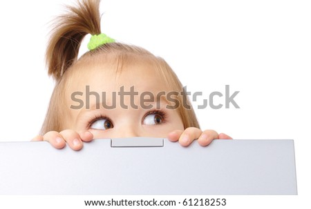 Cute little girl is looking out from her laptop, isolated over white