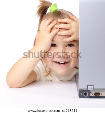 Cute little girl is looking out from laptop, holding her head in astonishment, isolated over white