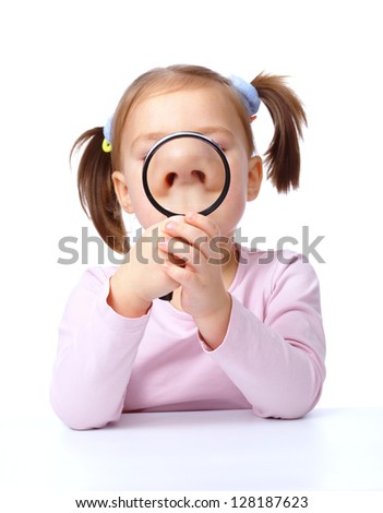 Cute little girl is looking through magnifier, isolated over white
