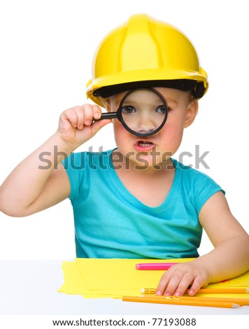 Cute little girl is looking through magnifier wearing hard hat, isolated over white