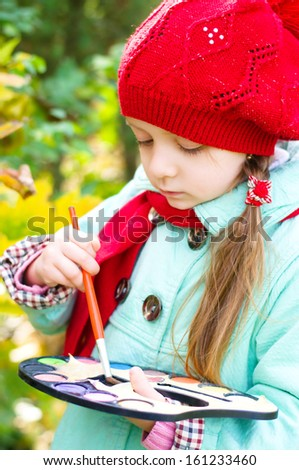 cute little girl is painting outdoors