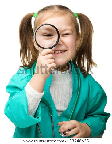 Cute little girl is playing doctor with magnifier, isolated over white