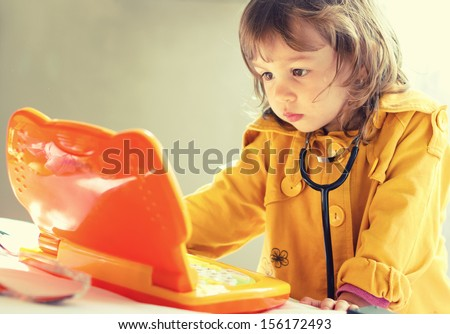 Cute little girl is playing doctor with stethoscope and laptop toy