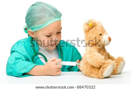 Cute little girl is playing doctor with syringe and teddy bear, isolated over white