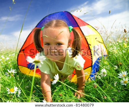 Cute little girl is playing outdoors under tent