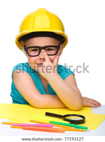 Cute little girl is playing while wearing hard hat, isolated over white - stock photo