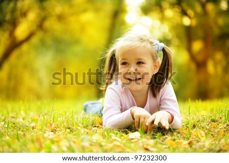 Cute little girl is playing with leaves in autumn park