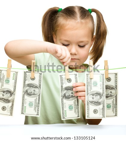 Cute little girl is playing with paper money - dollars, isolated over white