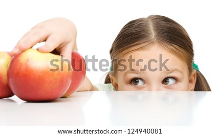 Cute little girl is reaching apple on table, isolated over white