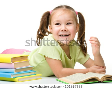 Cute little girl is reading a book while laying on floor, isolated over white