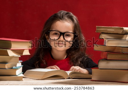 Cute little girl is reading a book while wearing glasses, isolated over red
