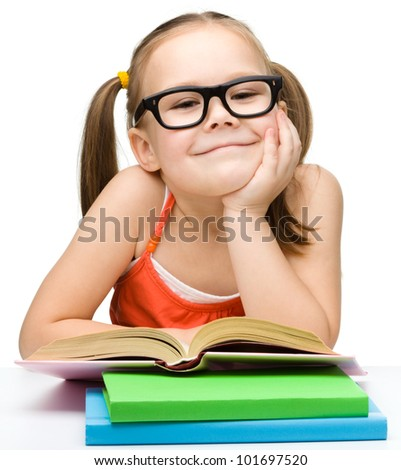 Cute little girl is reading book wearing glasses, isolated over white - stock photo