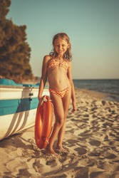 Cute little girl is relaxing on the beach. She is standing next to boat and sunbathing.