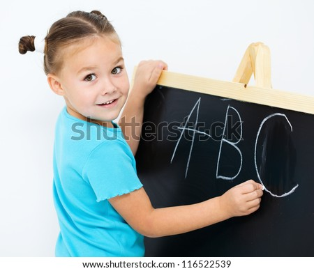 Cute little girl is showing letter E on the alphabet in preschool - stock photo