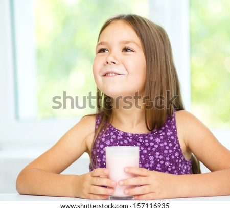 Cute little girl is showing milk moustache
