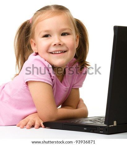 Cute little girl is sitting on floor with her black laptop, isolated over white