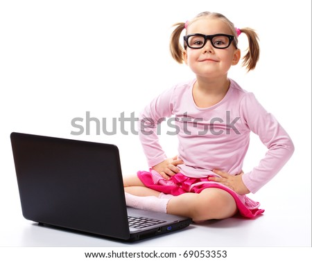 Cute little girl is sitting on floor with her laptop, wearing glasses, isolated over white