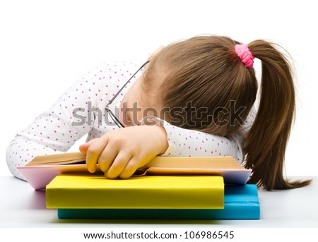 Cute little girl is sleeping on a book while wearing glasses, isolated over white