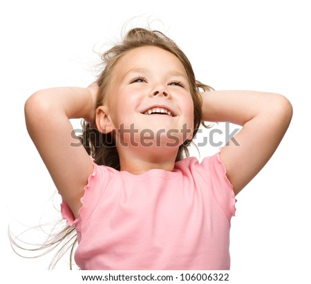 Cute little girl is stretching and rising hands up in happiness looking high, isolated over white