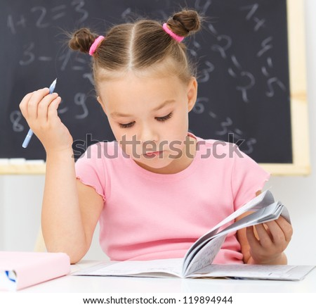 Cute little girl is studying in school - stock photo