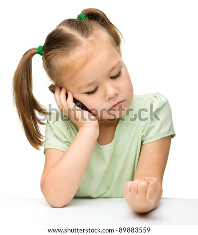 Cute little girl is talking on a cell phone while sitting at table, isolated over white
