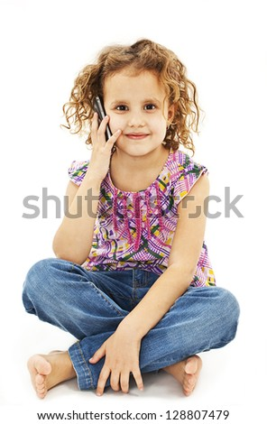 Cute little girl is talking on cell phone. Isolated on white background.