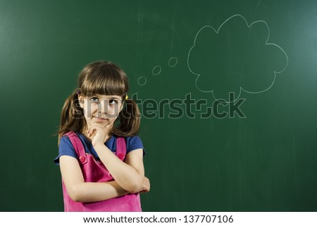 Cute little girl is thinking in front of blackboard Little girl thinking