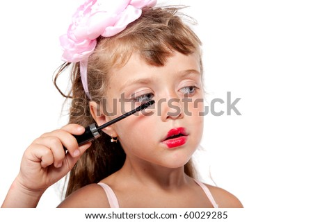 Cute little girl is trying painting her eyelashes