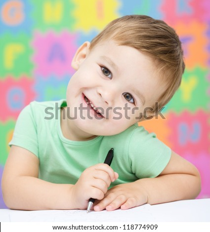 Cute little girl is writing using a pen in preschool