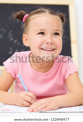 Cute little girl is writing using a pen in school