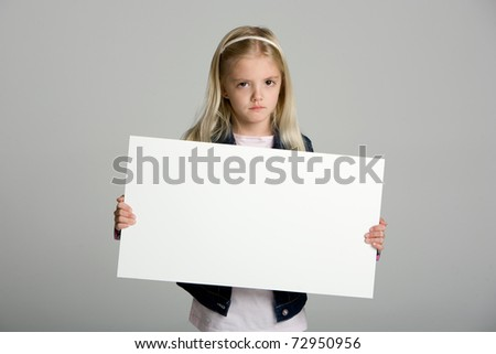 Cute little girl isolated on neutral background holding sign - stock photo