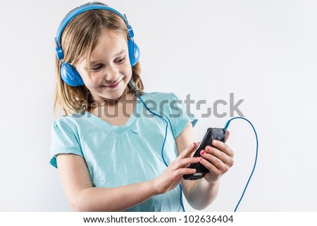 Cute little girl jamming to music on mobile device with blue shirt headphones, smiling at screen, making selection