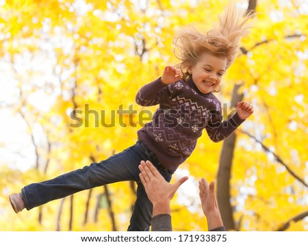 Cute little girl jumping in the autumn forest