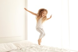 Cute little girl jumping on white bed