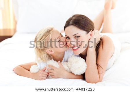 Cute little girl kissing her mother lying on a bed