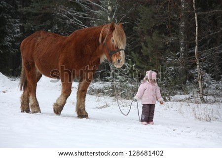 Cute little girl leading big draught horse by the forest in winter