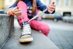 Cute little girl learning to tie shoelaces outdoors on summer day